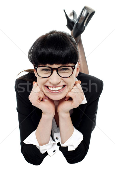 Woman relaxing on floor with hands on her cheeks Stock photo © stockyimages