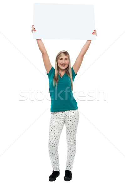 Woman holding ad board above her head Stock photo © stockyimages