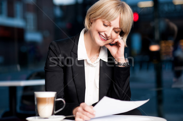 Female reviewing business report in cafe Stock photo © stockyimages
