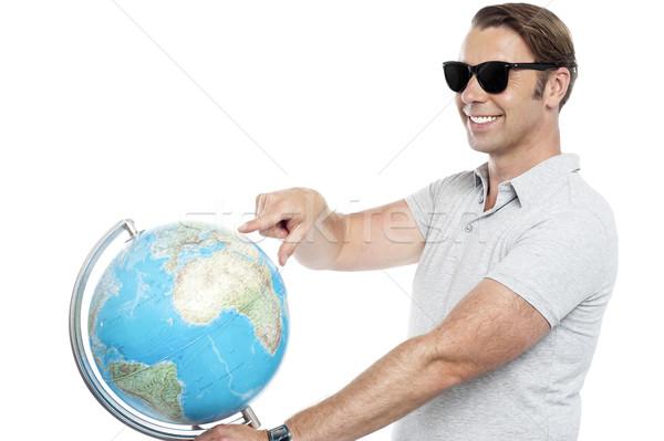 Jóképű fickó védőszemüveg mutat földgömb izolált Stock fotó © stockyimages