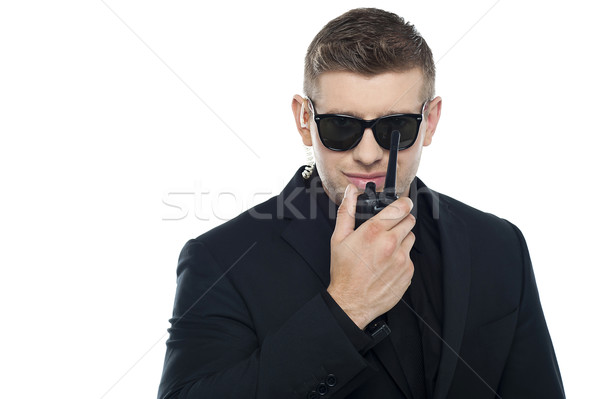 Smart young security personnel communicating over the walkie-talkie Stock photo © stockyimages