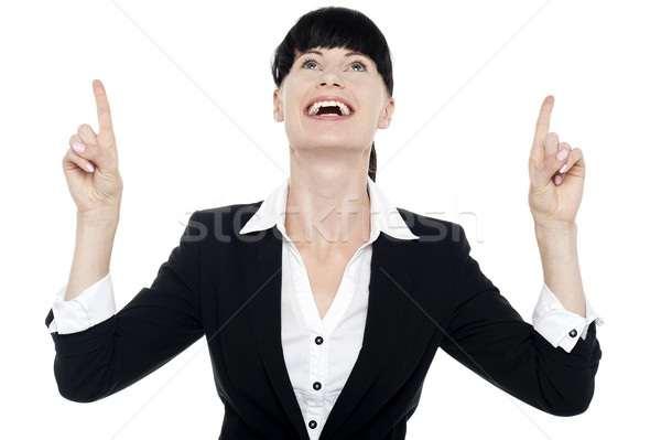 Excited businesswoman looking ad pointing upwards Stock photo © stockyimages