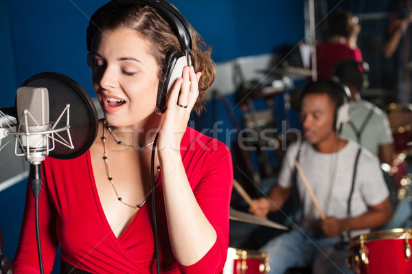 Lady singing in recording studio Stock photo © stockyimages
