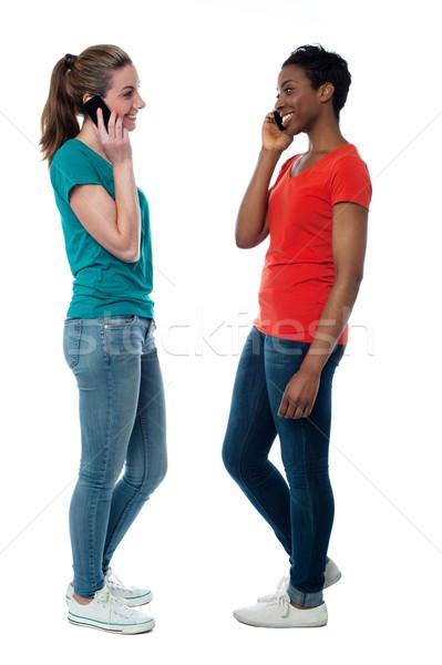 Stock photo: Trendy females speaking over cellphone