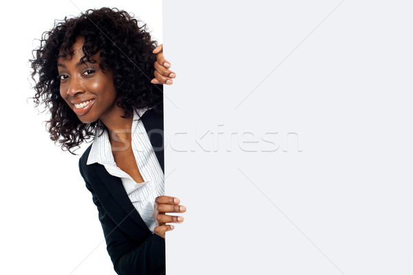 Woman peeping from behind white placard Stock photo © stockyimages