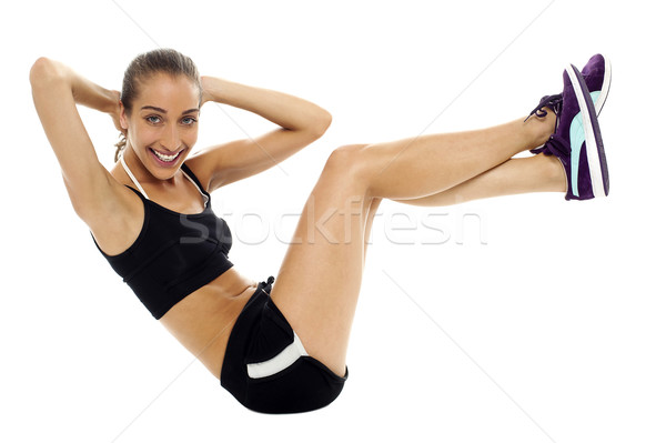 Fit woman in sporty attire doing crunches Stock photo © stockyimages