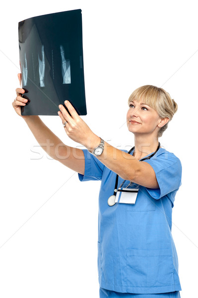 Stock photo: Orthopedic surgeon holding up x-ray to analyze