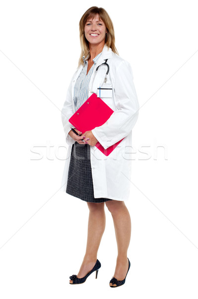 Smiling female physician holding clipboard Stock photo © stockyimages