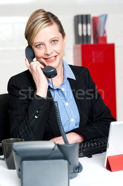 Pretty front desk lady attending clients call Stock photo © stockyimages