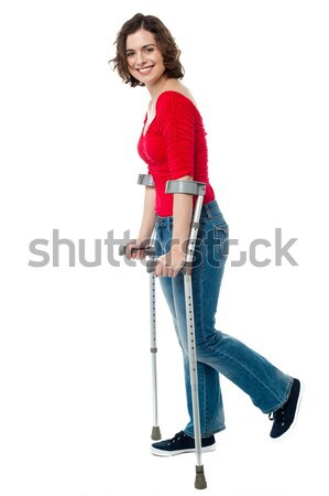 Young woman walking with crutches Stock photo © stockyimages