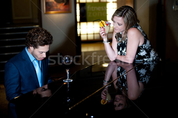 Woman enjoying cocktail and admiring man playing piano Stock photo © stockyimages