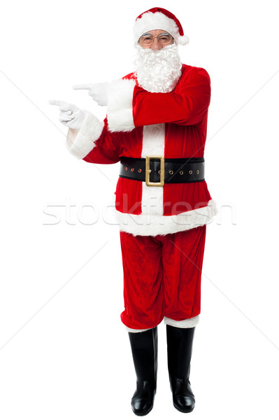 Stock photo: Man in Santa costume indicating at copy space area