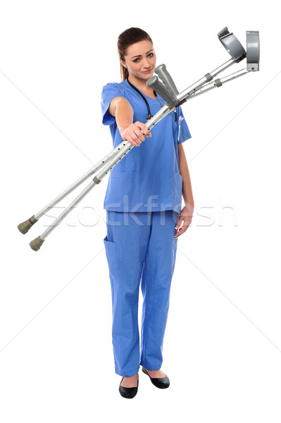 Sullen faced doctor displaying crutches Stock photo © stockyimages