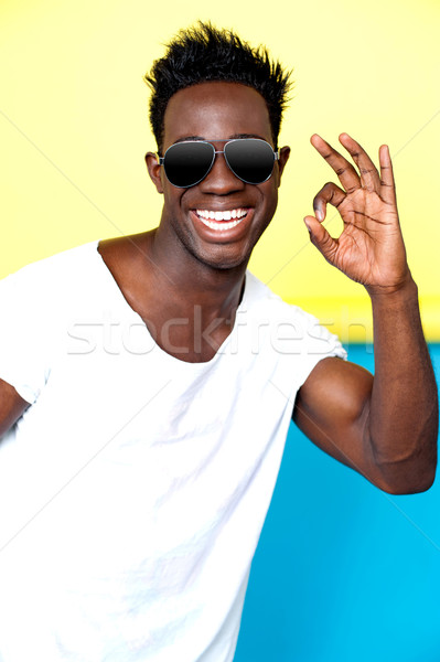 Smiling young man gesturing excellence Stock photo © stockyimages