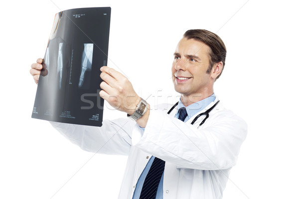 Experienced orthopedic surgeon reviewing x-ray report Stock photo © stockyimages