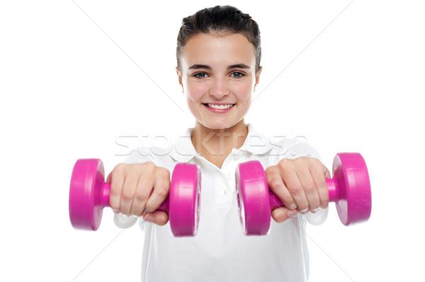 Image jeune fille posant haltères souriant caméra Photo stock © stockyimages