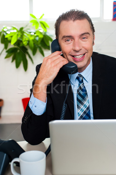 Smiling male manager attending clients call Stock photo © stockyimages
