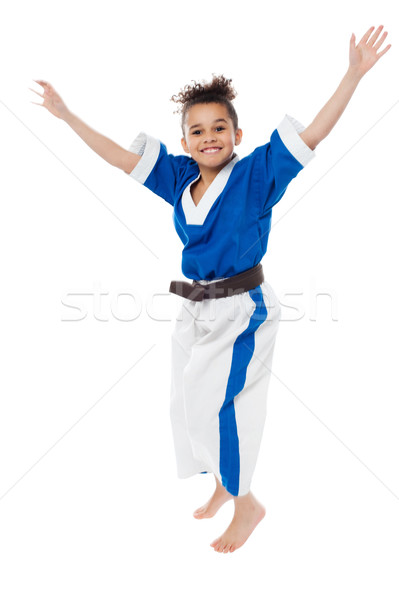 Enthusiastic young girl kid in karate uniform Stock photo © stockyimages