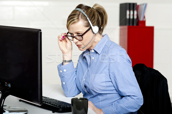Business lady reviewing report closely Stock photo © stockyimages