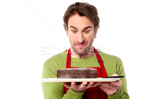 Male chef holding yummy chocolate cake Stock photo © stockyimages