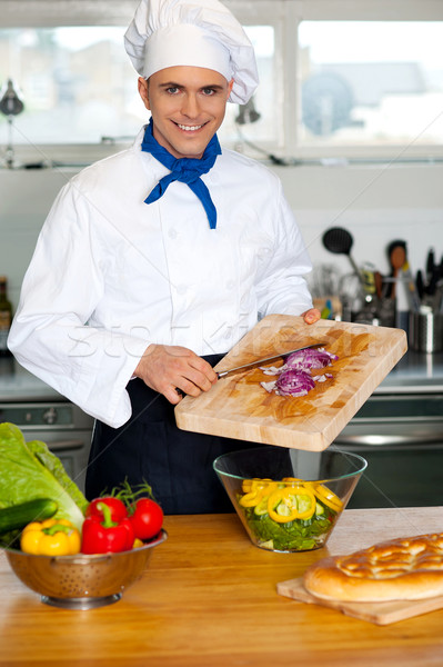 Chef putting vegetables in a bowl Stock photo © stockyimages