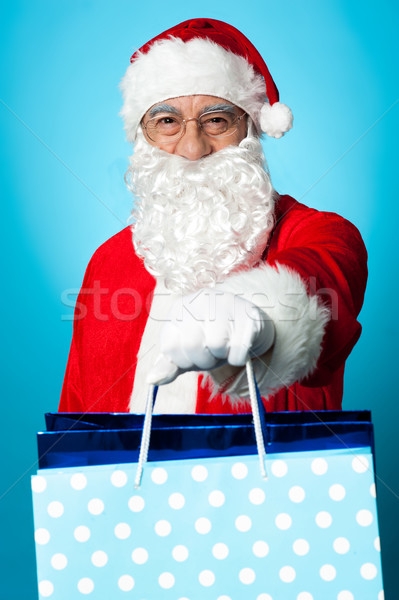 Santa holding shopping bags in his outstretched arms Stock photo © stockyimages