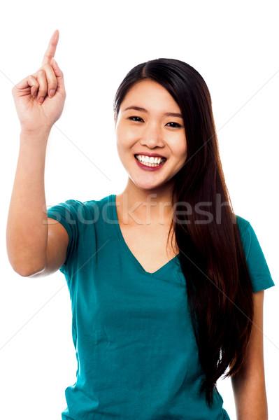 Smiling girl pointing upwards Stock photo © stockyimages