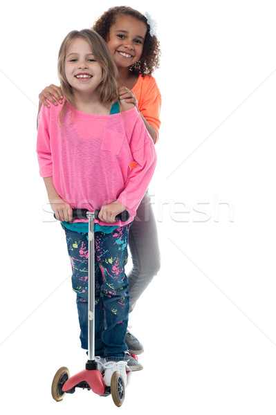 Happy little girls on scooter Stock photo © stockyimages