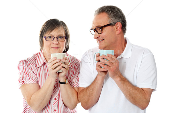 Happy matured couple holding cofee mug Stock photo © stockyimages