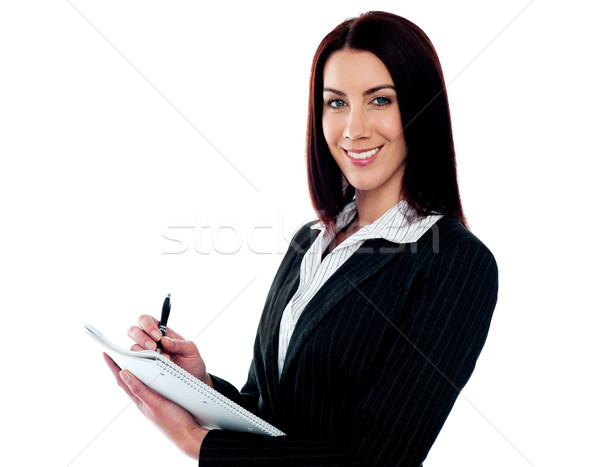 Young beautiful businesswoman writing on clipboard Stock photo © stockyimages