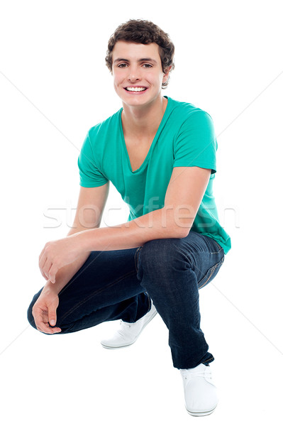 Cool guy wearing white sneakers, squatting posture Stock photo © stockyimages