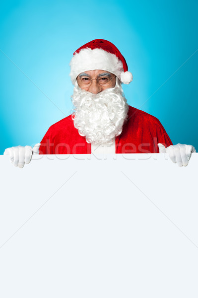Aged Santa standing behind a blank ad board Stock photo © stockyimages