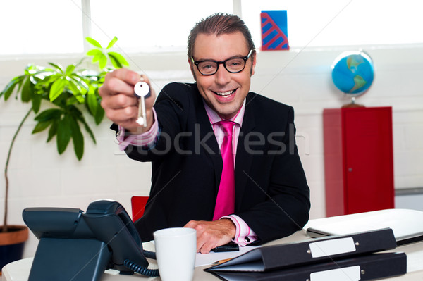 Happy male executive handing over the keys Stock photo © stockyimages