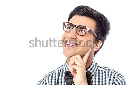 Smiling young man daydreams and looks up Stock photo © stockyimages
