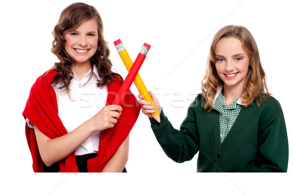 Smiling teenagers making cross sign with pencil Stock photo © stockyimages