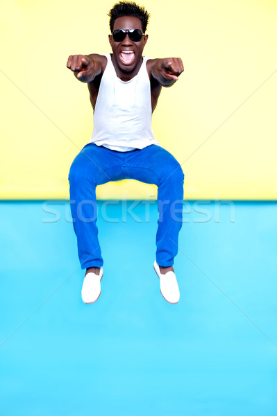 Excited male jumping and pointing at you Stock photo © stockyimages
