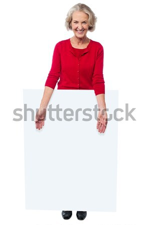 Joyous lady standing behind blank banner ad Stock photo © stockyimages