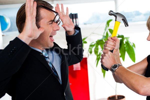 Woman threatening her boss, holding hammer. Stock photo © stockyimages