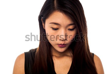 Sad young girl looking downwards Stock photo © stockyimages
