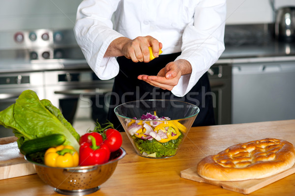 Male chef put ingredient in the glass bowl Stock photo © stockyimages