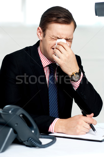 Young man having severe cold. Sneezing Stock photo © stockyimages