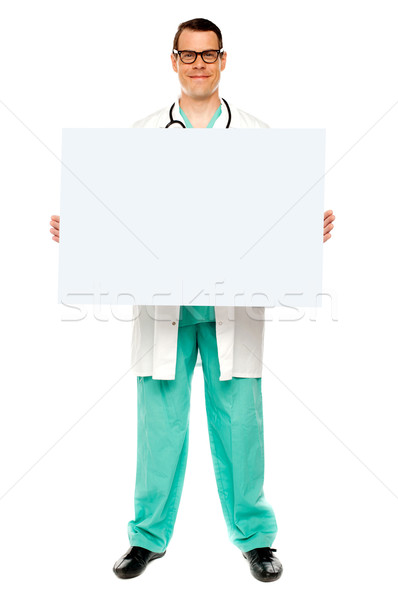 Male doctor displaying white advertising board Stock photo © stockyimages