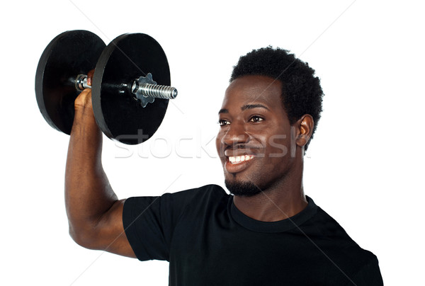 Powerful muscular young man lifting weights Stock photo © stockyimages
