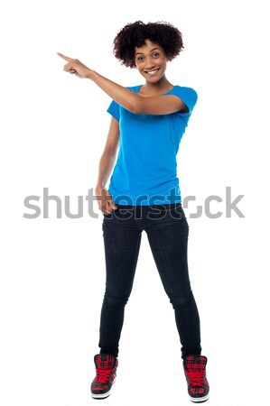 Attractive young woman pointing sideways Stock photo © stockyimages