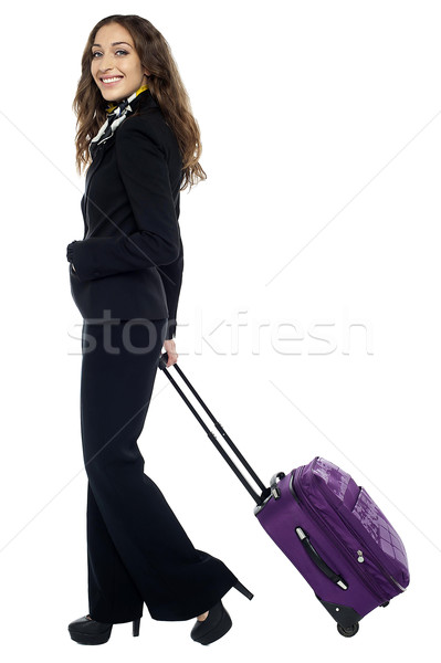 Shot of a brunette dragging her strolley Stock photo © stockyimages