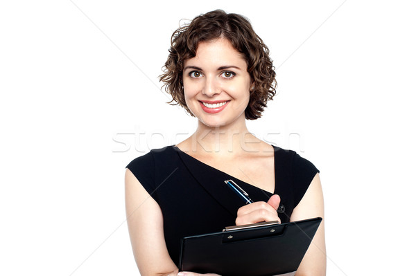 Charming woman writing notes on clipboard Stock photo © stockyimages