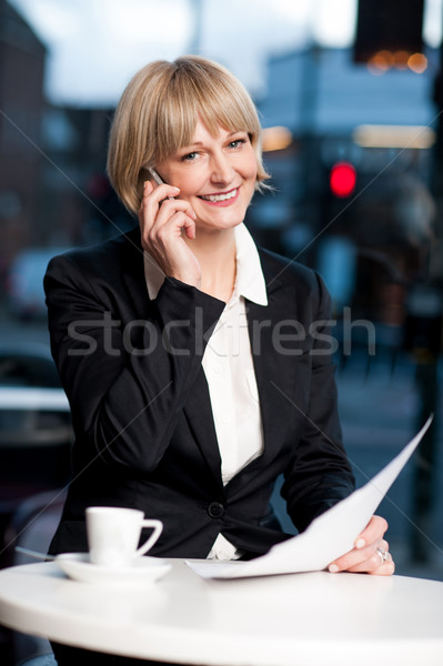 Manager communicating via cell phone in cafe Stock photo © stockyimages