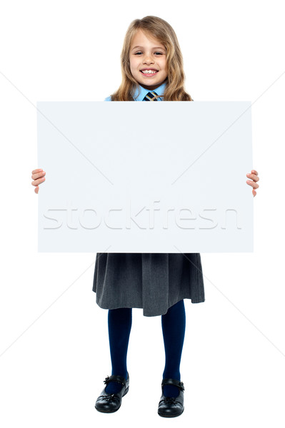 Cheerful schoolkid showcasing blank whiteboard Stock photo © stockyimages