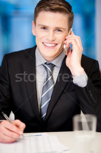 Mosolyog vállalati fickó telefonbeszélgetés fiatal üzletember Stock fotó © stockyimages