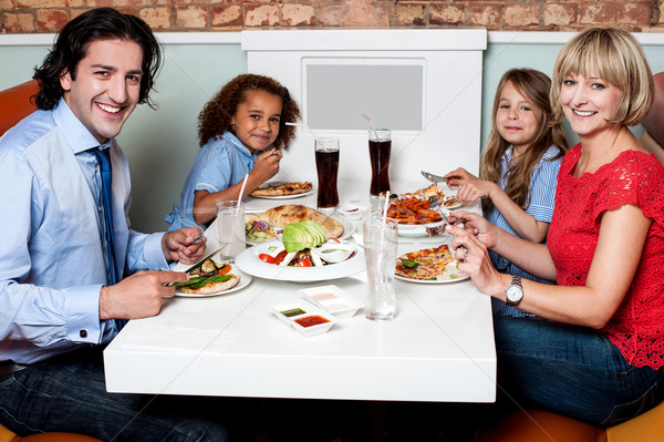 Family eating together in a restaurant Stock photo © stockyimages